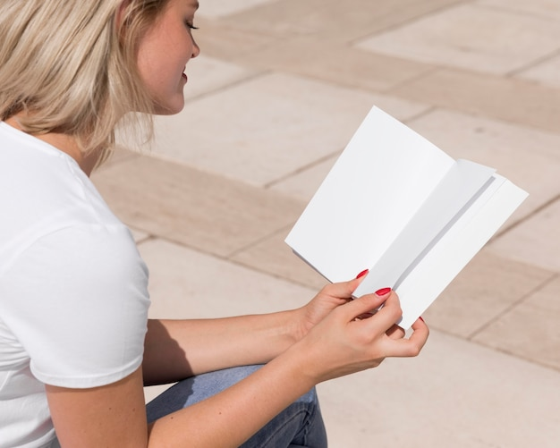 Woman enjoying reading a book outdoors