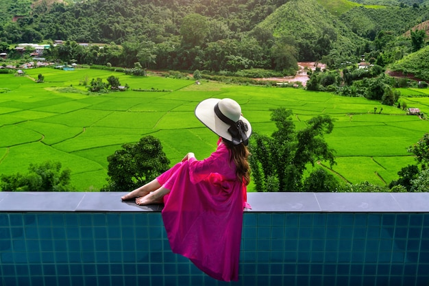 Woman enjoying rice terrace viewpoint and green forest in nan, thailand