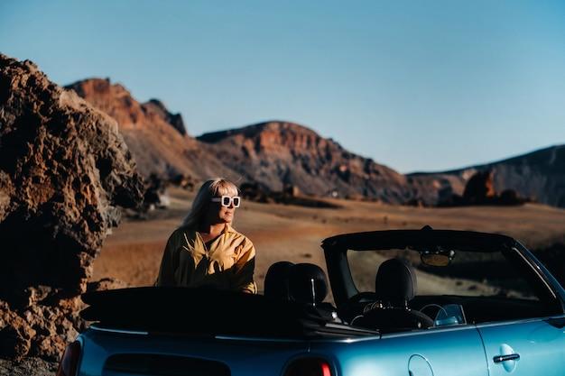 スペイン、テネリフェ島の火山の山の森の道端にあるコンバーチブル車の近くに地図を持って立って、ロードトリップを楽しんでいる女性。