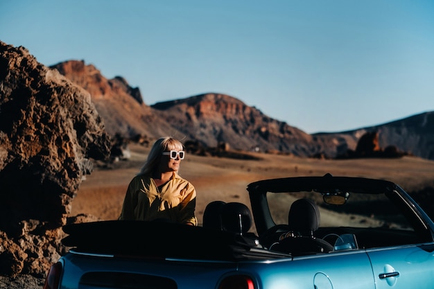 Woman enjoying road trip, standing with map near convertible car on the roadside in the volcanic mountain forest on tenerife island, spain.