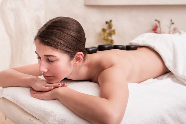 Woman enjoying rock therapy at spa