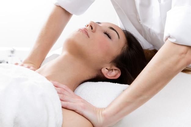 Woman enjoying shoulder massage at beauty spa