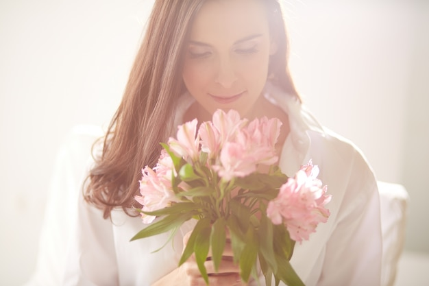 Woman enjoying and smelling a bouquet