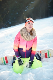 丘の上でスノーボードを楽しんでいる女性