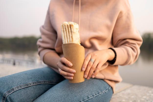 Женщина, наслаждающаяся уличной едой на открытом воздухе
