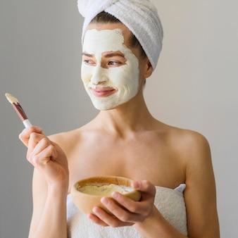 Женщина наслаждаясь днем курорта дома пока носящ лицевой щиток гермошлема