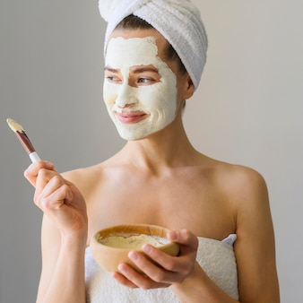 Woman enjoying spa day at home while wearing face mask