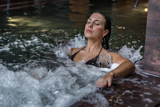Женщина, наслаждающаяся спа-процедурой в гидромассажной ванне