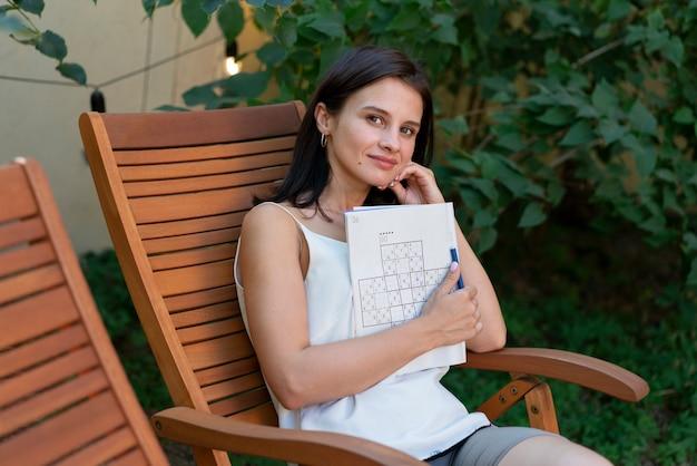 Donna che si gode da sola un gioco di sudoku su carta
