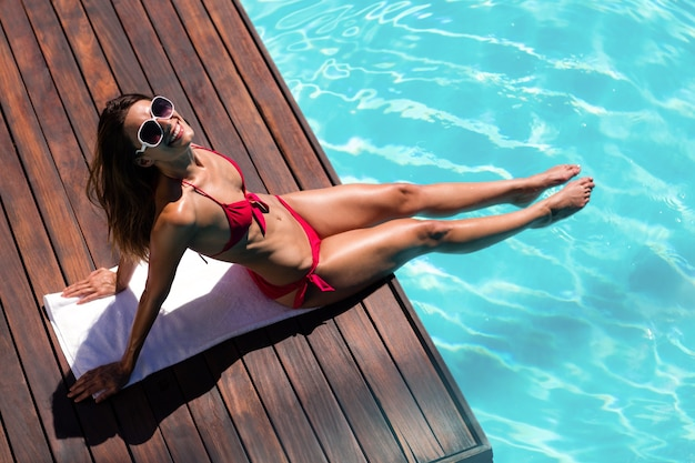 プールの端で日光浴を楽しんでいる女性