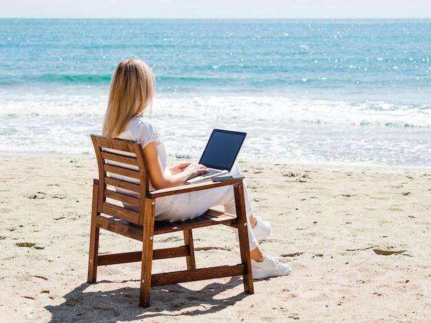 ノートパソコンで作業しながらビーチを楽しむ女性
