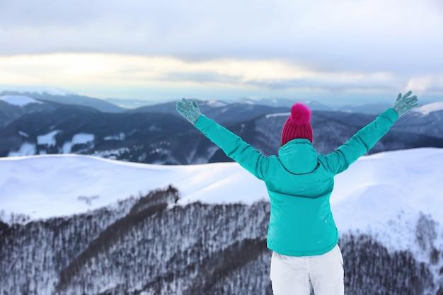 雪山リゾートの美しさを楽しむ女性。冬休み