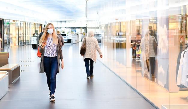 쇼핑몰에서 하루를 즐기는 여자. 안면 마스크.