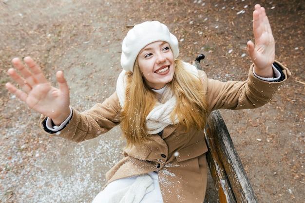 Женщина наслаждается снегопадом, сидя на скамейке в парке