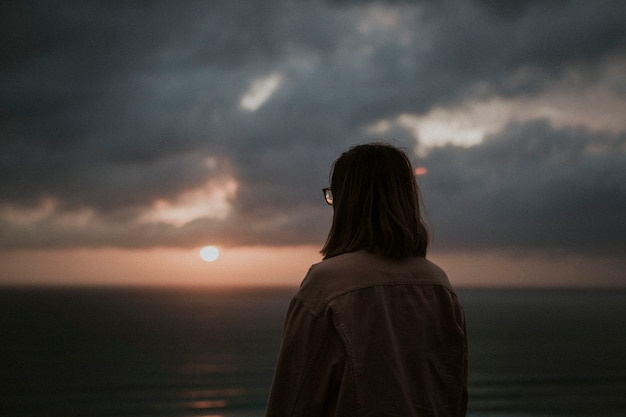 Женщина, наслаждаясь восходом солнца на скале на пляже