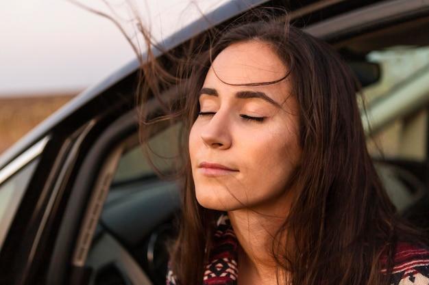 屋外で彼女の車の座席から風を楽しむ女性