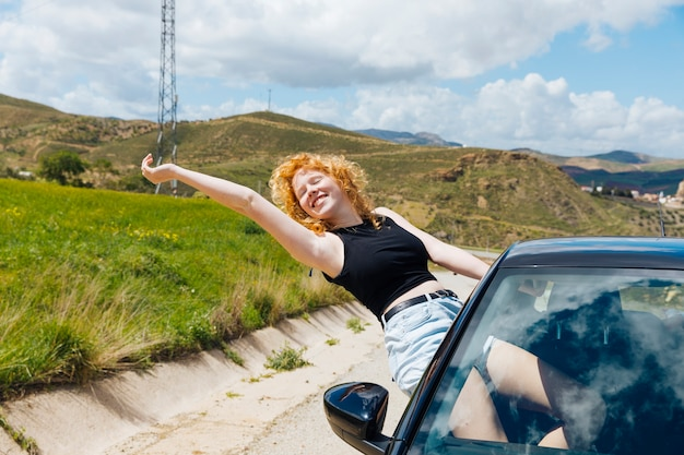 Woman enjoying trip out of car window and stretching out arm with closed eyes