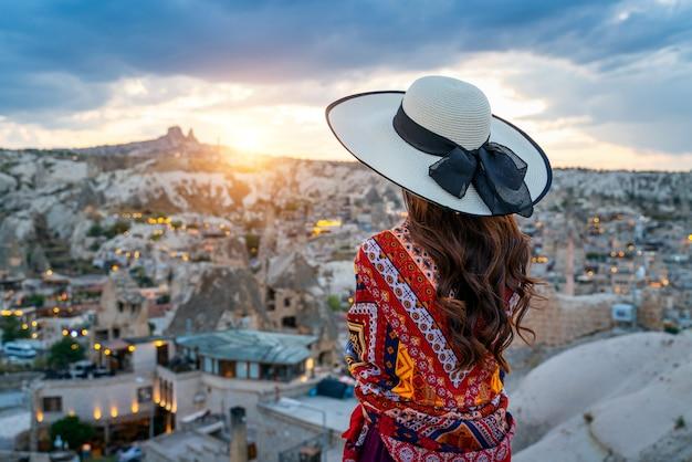 Женщина, наслаждаясь видом на город гереме, каппадокия в турции.