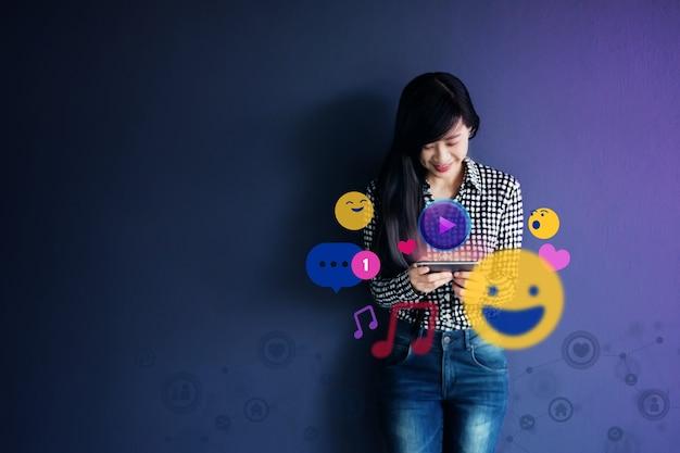 Женщина, наслаждаясь при использовании приложения социальных сетей через мобильный телефон. образ жизни современной женщины. окруженный множеством икон