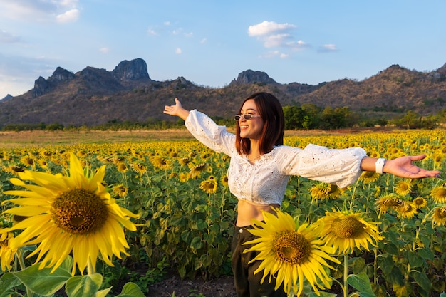 Woman enjoying with sunflower field at kao jeen lae in lopburi, thailand