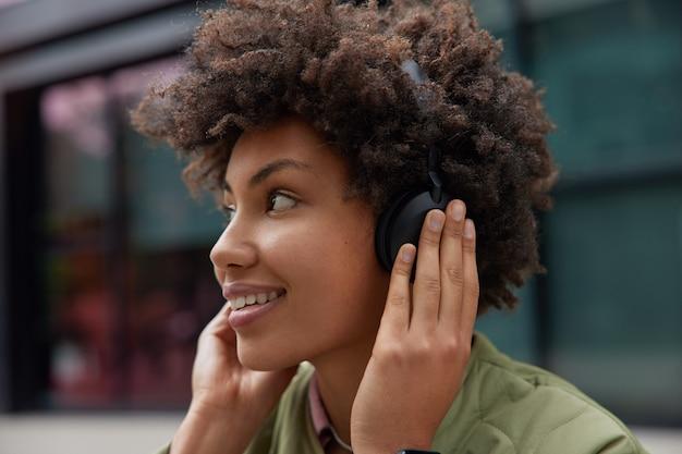 La donna gode della traccia audio nelle cuffie wireless utilizza l'applicazione per ascoltare le canzoni si sente felice si prepara per l'allenamento cardio riposa in un ambiente urbano ama la sua nuova attrezzatura stereo