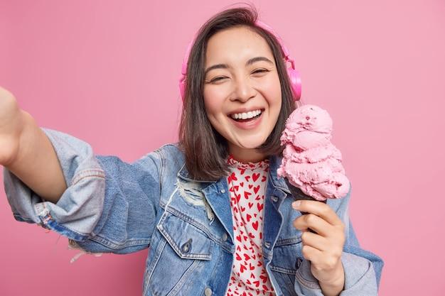 La donna si diverte a mangiare un delizioso cono gelato durante l'estate pone per selfie sorrisi ascolta ampiamente musica tramite le cuffie vestita con una giacca di jeans si diverte