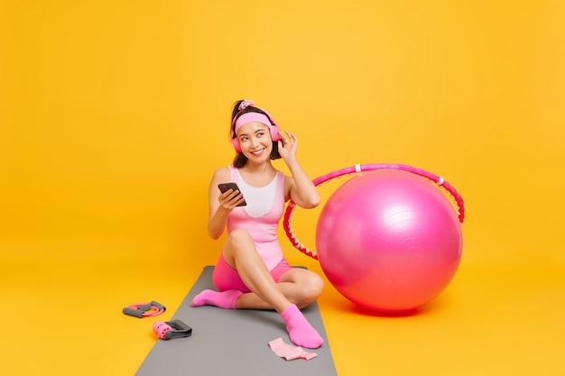 女性はプレイリストからお気に入りの音楽を楽しんでいますワイヤレスヘッドフォンを着用携帯電話を保持しますフィットネスマットの上に座って黄色の壁で隔離された国内トレーニングの後にスポーツ休憩に行きます