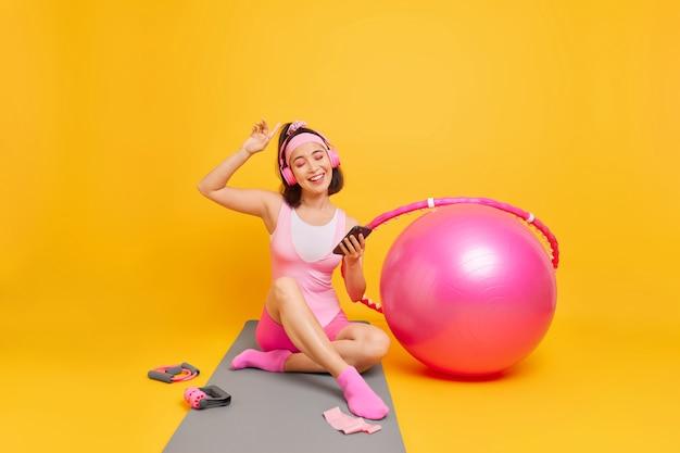 여자는 좋아하는 플레이리스가 휴대전화를 들고 활동복을 입은 스테레오 헤드폰을 들고 집에서 매트 기차에 앉아 피트니스 공 훌라후프 확장기를 사용합니다.