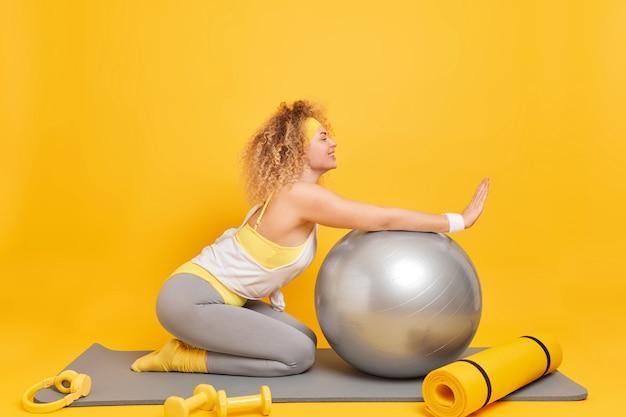 La donna gode dell'allenamento fitness a casa si appoggia alla palla svizzera pone sul tappetino con manubri karemat e cuffie intorno isolato su giallo