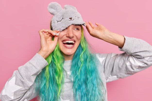 Woman enjoys good morning after awakening wears sleepmask on forehead smiles broadly greets new day has long dyed hair dressed in pajama looks away happily poses indoor