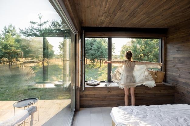 Женщина наслаждается отдыхом в загородном доме или отеле с распростертыми руками возле панорамных окон с видом на сосновый лес. доброе утро и отдых на природе. вид сзади. копировать пространство