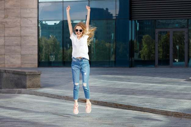A woman enjoys and jumps in the summer outside the building summer holidays