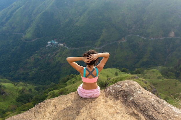 Woman enjoys a mountain view while standing on a cliff