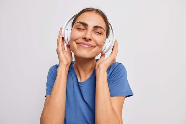 Woman enjoys pleasant melody in wireless headphones catches every bit of song keeps eyes closed dressed in casual blue t shirt on white