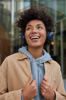 女性はポジティブなオーディオブックを楽しんでいます音楽を聴いて自由な時間を過ごしてうれしいパーカーを着てジャケットのポーズはエネルギッシュなプレイリストが好きです