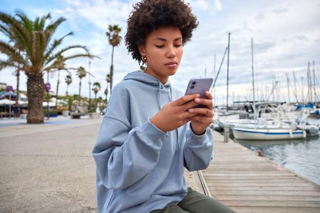女性はソロツーリズムの経験を楽しんでいます。カジュアルな服を着たネットワーキングに最新のスマートフォンガジェットを使用しています。桟橋でポーズをとるメッセージを読んでブログに掲載