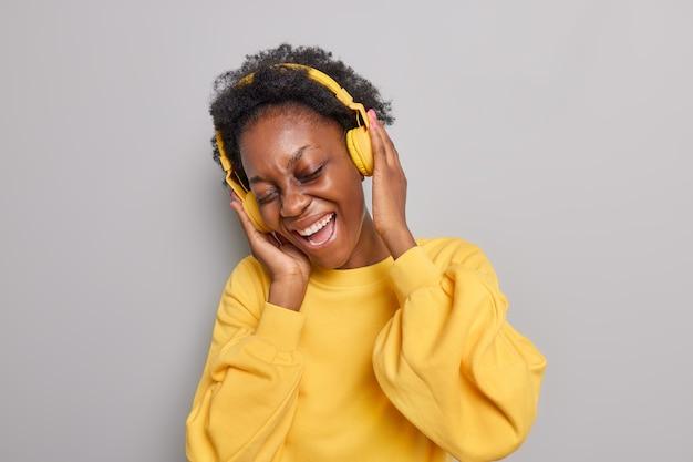 女性はワイヤレスでステレオサウンドを楽しんでいます現代のヘッドフォンはカジュアルな黄色のジャンパーを着て目を閉じたままにします灰色で隔離された音楽を聴くのが好きです