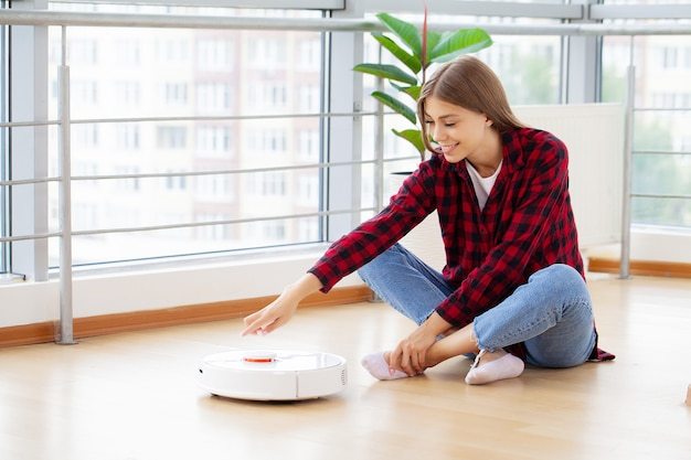 Женщина наслаждается работой умного робота-пылесоса.