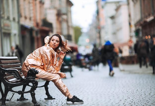 La donna gode il vento seduto sulla panchina sulla strada