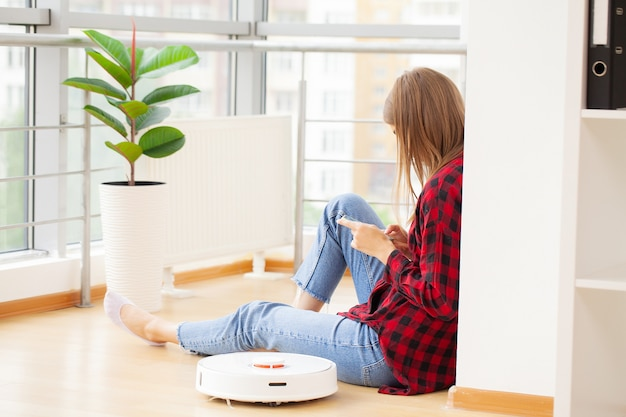 Woman enjoys the work of a smart robot vacuum cleaner.