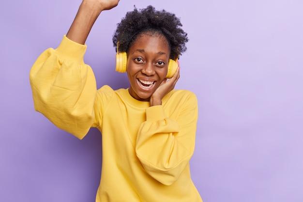女性はcovid19の検疫中に自宅で楽しませ、ヘッドフォンで音楽を聴き、紫で分離されたお気に入りの曲を楽しんでいます