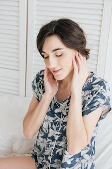 여자는 열정적으로 lapto와 헤드폰에서 음악을 듣습니다.