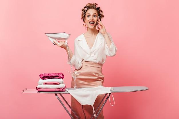 Женщина с энтузиазмом разговаривает по телефону во время глажки одежды