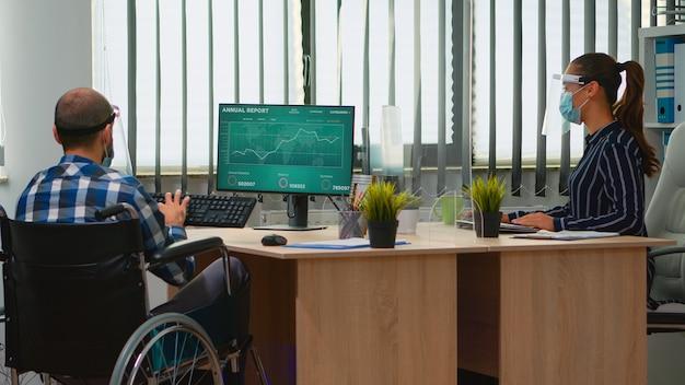 新しい通常の営業所で働く保護バイザーを身に着けている車椅子で職場に動けなくなったビジネスマンを連れてくる女性起業家。社会的距離を尊重するマスクを持つビジネスマン