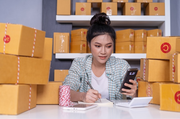 Woman entrepreneur checking and writing order with cardboard