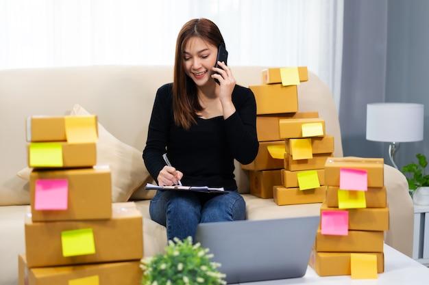 Женщина-предприниматель разговаривает с клиентом по мобильному телефону и пишет заказ продукта в домашнем офисе
