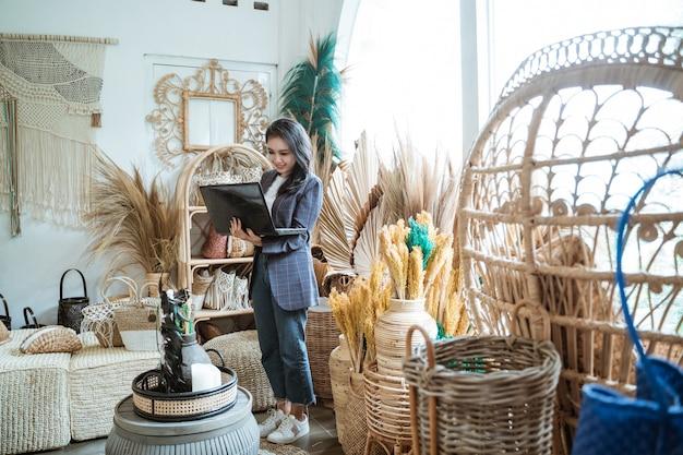 Женщина-предприниматель с помощью ноутбука, стоя среди экзотических изделий ручной работы в магазине для рукоделия