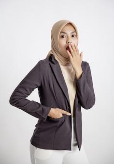 Женщина-предприниматель в хиджабе удивлена, глядя в камеру, концепция офисной работы изолирована на белом фоне