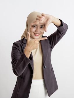 ヒジャーブを身に着けている女性起業家は、写真のサインの手のポーズ、事務概念の分離された白い背景を撮る