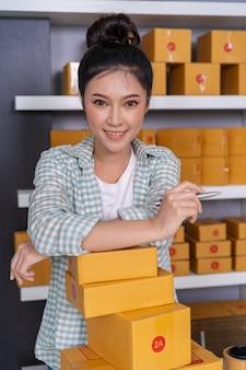 自宅で自分の仕事を買い物するオンラインビジネスの小包箱を持つ女性の起業家